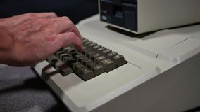 Typing on retro old fashioned personal computer profile shot. Profile shot of someone typing on an old-style 1980s personal computer. Shallow depth of field stock video