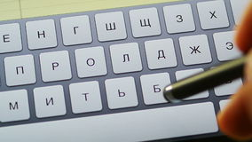 Typing Russian on tablet computer. Hand holding stylus typing fast text messages on smart tablet or phone in Russian language stock video
