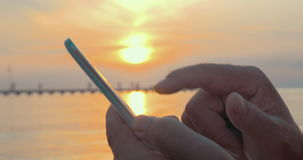 Typing in Smartphone at Sunset stock video