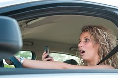 Typing SMS while driving car Royalty Free Stock Images