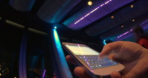 Typing sms at nightclub. Close-up and wide angle shot of female hand texting on touschscreen smart phone at nightclub. Lighting changing colors stock video footage