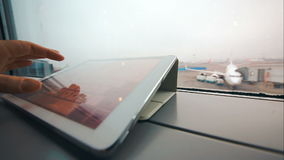 Typing on tablet computer on windowsill at airport. Close-up shot of woman hand typing on tablet PC by the window. Airport area and boarding plane in background stock video