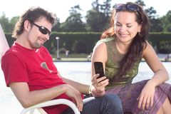 Typing text message. A woman typing a text message while the man is sitting and looking at the mobile phone Royalty Free Stock Photo