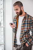 Typing text message. Confident young bearded man typing message on his smart phone while standing near the window Royalty Free Stock Photo