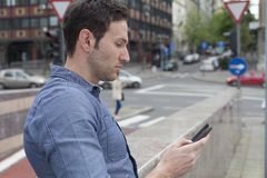 Typing text message. Man typing text message, street Stock Photo