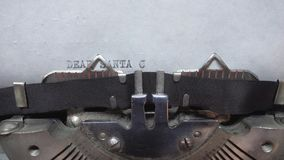 Typing text at the typewrite. Typing DEAR SANTA CLAUS at the typewriter stock video