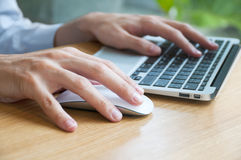 Typing and Using Mouse. Man typing and using a mouse and a laptop Royalty Free Stock Photography
