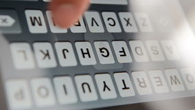 Typing on a virtual keyboard of touch screen.  stock video