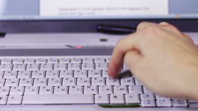 Typing on a White Computer Laptop Keyboard. A man working at a laptop sitting at a wooden table on which there are more laptop and tablet with a moving picture stock video