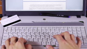Typing on a White Computer Laptop Keyboard. A man working at a laptop sitting at a wooden table on which there are more laptop and tablet with a moving picture stock footage