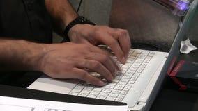 Typing on white laptop computer. Man wearing black short sleeve shirt is typing fast on white keyboard of laptop computer stock footage