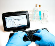 Typing on a wireless keyboard in the laboratory. Gloved hands of a laboratory worker type data into a spreadsheet on a tablet computer using a wireless keyboard Stock Image