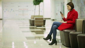 Typing woman on a smartphone device. Sitting in the mall stock video footage