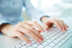 Typing worker. Female office worker typing on the keyboard Stock Images