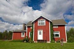 Typisch rood Skandinavisch huis met wolken, blauwe hemel en goed gegeven gras stock fotografie