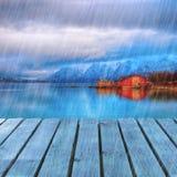 Typisch Skandinavisch Rood huis op overzees in fjord met platformdok in regenachtige dag Stock Fotografie