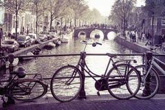Typische Amsterdam-Fahrräder, -brücken u. -kanäle stockfotografie