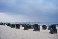 Typische deutsche Strandstühle oder Strandstuhlkörbe auf dem Strand von Nord oder von Ostsee am Abend Stockfotos