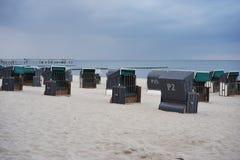 Typische Duitse ligstoelen of ligstoelenmanden op het strand van Nord of Oostzee in de avond stock fotografie