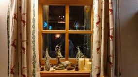 Typische Fenster des Gebirgshölzernen Chalets mit Weihnachtsdekorationen zur Winterzeit stockfotografie