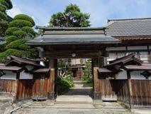 Typische Japanse houten die ingangspoort door sommige bomen wordt omringd stock foto's