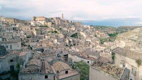 Typische mening van stenen (Sassi di Matera) en kerk van Matera onder blauwe hemel stock footage