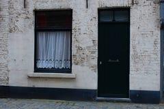 Typische middeleeuwse de bouwvoorgevel in Europa Groen houten gesloten deur en venster met wit gordijn Royalty-vrije Stock Foto's
