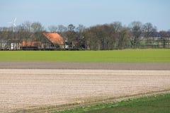 Typische niederländische Polderlandschaft mit Bauernhaus und entblößen Felder Stockfotos