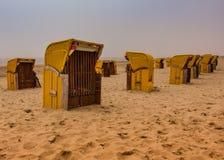 Typische niederländische Retro- beachchairs, die auf dem Strand des Nordens sitzen lizenzfreie stockfotografie