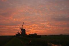 Typische niederländische Windmühlen werden gegen einen orange Glättungshimmel silhouettiert lizenzfreie stockfotografie