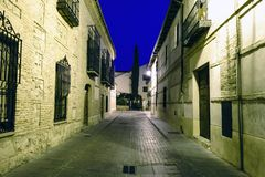 Typische Pflasterstraße mit Fassaden von alten Häusern während der blauen Stunde in Alcala de Henares, Spanien Ohne Leute und mit lizenzfreie stockfotos
