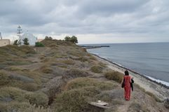 Typische Santorini-Bucht mit Dame im Rot und in der Seeansicht lizenzfreies stockfoto