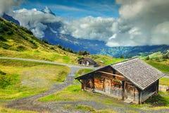 Typische Schweizer alpine Bauernhäuser und schneebedeckte Berge, Bernese Oberland, die Schweiz Stockbild