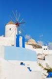 Typische witte windmolen op straat van Oia dorp stock afbeelding