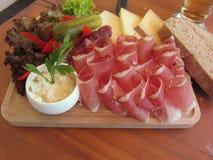 Typische Zuiden Tiroolse snack met vlek, bergkaas, mierikswortelsaus en geheel korrelbrood stock afbeeldingen