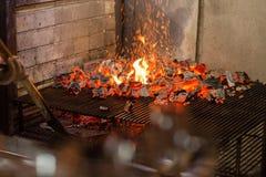 Typischer argentinischer Grill oder asado Brennendes Holz im Grill und in den glühenden Kohlen Stockfotografie