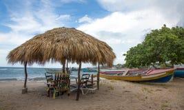 Typischer jamaikanischer Strandschutz und Fischerboote Stockfotos