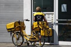Typischer Postwoman in Deutschland mit gelbem Fahrrad Lizenzfreie Stockfotografie