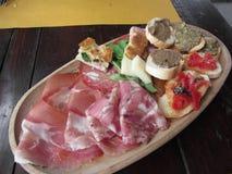 Typischer rustikaler toskanischer Aperitif mit crostini, Prosciutto, Schweinskopfsülze, Salami, Käse auf einem hölzernen Behälter Lizenzfreie Stockbilder