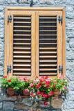 Typisches Fenster eines Steinhauses mit hölzernen Fensterläden schloss und Stockfotografie