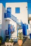Typisches Haus mit blauen Balkonen, Treppe und Blumen Kleines Mädchen auf Treppe im traditionellen griechischen Haus Schön Lizenzfreie Stockfotos
