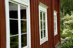 Typisches rotes skandinavisches Holzhaus mit weißen Fenstern Lizenzfreies Stockbild
