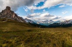 Typisk alpin äng som inramas av steniga alpina massiver av dolomitesna. Arkivbilder
