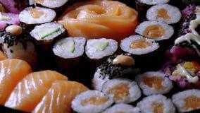 Typisk asiatisk mat - variation av olika sushistycken på den stora plattan stock video
