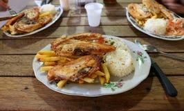 Typisk colombianskt mål - höna, ris, småfiskar, sallad royaltyfria foton