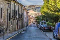 Typisk gata i nedstigning i staden av Siguenza och i bakgrunden kullarna av Guadalajara Castilla la Mancha Spanien arkivbilder