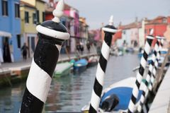 Typisk gataplats som visar brighly målade hus och att förtöja stolpar och kanalen på ön av Burano, Venedig arkivbild