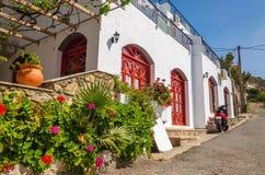 Typisk grekiskt hus med vita väggar och röda trädörrar Fotografering för Bildbyråer