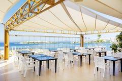Typisk hemtrevlig havsrestaurang med vita stolar Royaltyfri Bild