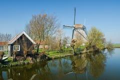 Typisk holländsk lantlig plats med lantgården och väderkvarnen och reflexion i kanalen framtill arkivbilder
